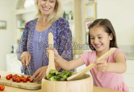 grandmother and granddaughter preparing salad in
