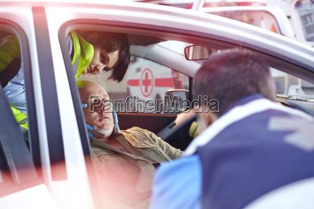 rettungskraefte in einem auto zum unfallopfer