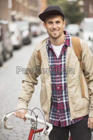 man drueckt fahrrad auf stadtstrasse