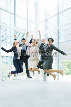 business people jumping in office building