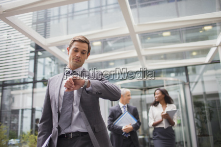 businessman looking at watch walking out