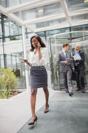 businesswoman talking on cell phone walking