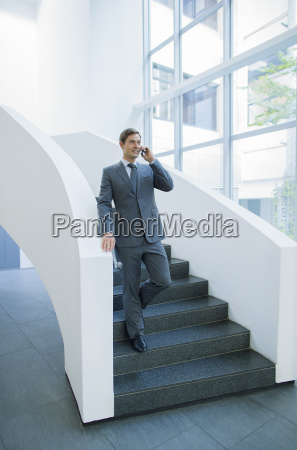 businessman talking on cell phone walking
