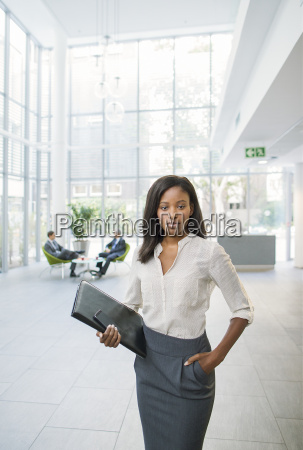 businesswoman holding binder in office building