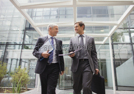 businessmen walking out of office building