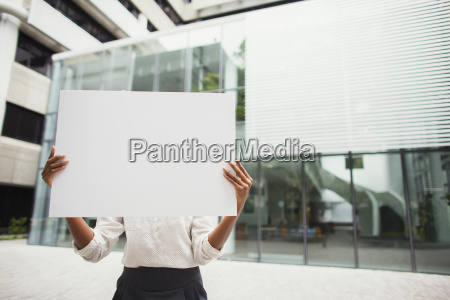 businesswoman holding cardboard outside of office