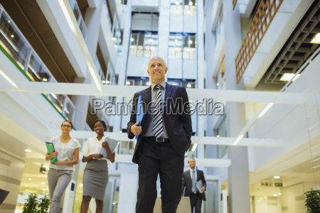 business people walking through office building