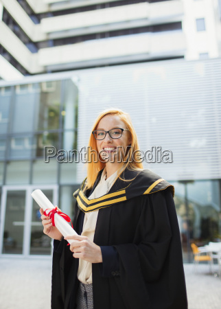 student in cap and gown holding