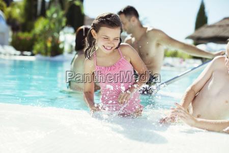 glueckliche kinder spritzen wasser im schwimmbad