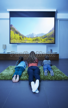 mother and children watching television in