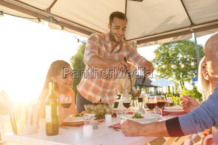 mann serviert salat am sonnigen terrasse