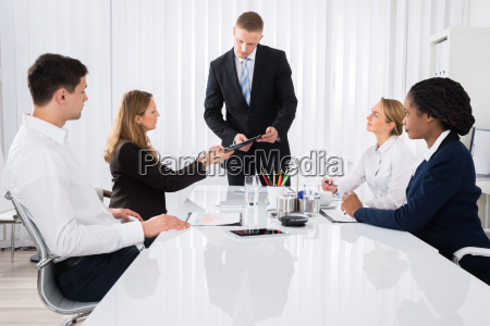 colleague showing document to businessman