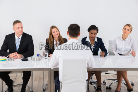 businesspeople interviewing man