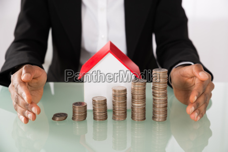 businesswoman protecting house model with stack