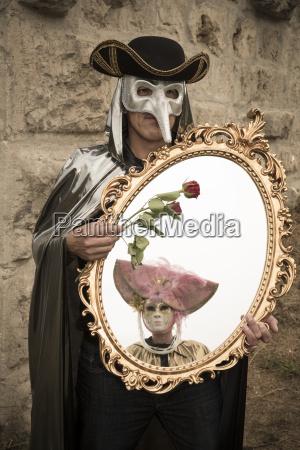 mann mit venezianischer vogel maske haelt