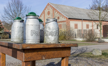milk cans stand on a wooden