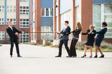male and female businesspeople playing tug
