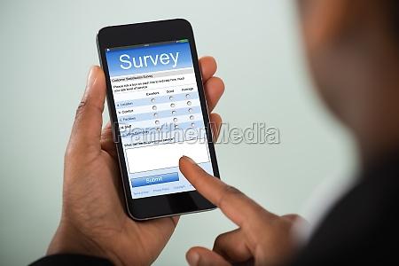 geschaeftsfrau fuellt online umfrage auf handy