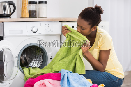 woman smelling clothes from washing machine