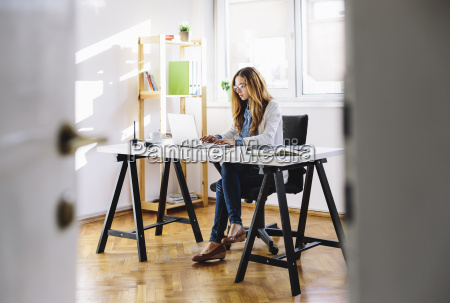 young woman working with laptop at