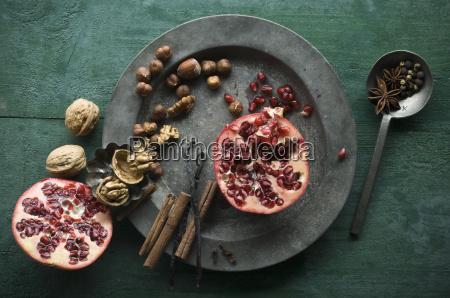 zwei haelften granatapfel verschiedene gewuerze und