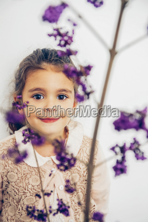portrait of smiling girl behind blossom
