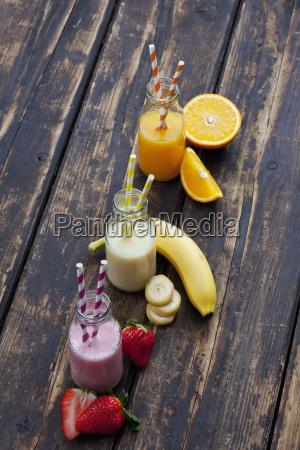 dreiergesange flaschen mit verschiedenen fruchtsmoothies und