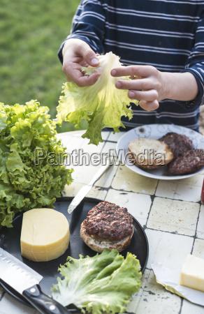 boys hands preparing hamburger