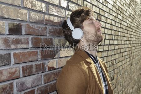 young man leaning against brick wall
