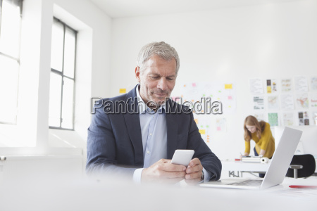 businessman in office at desk looking