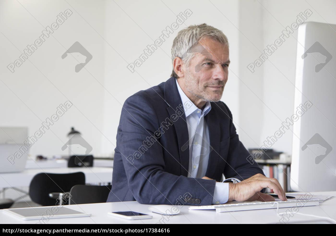 geschäftsmann, im, büro, am, schreibtisch, mit - 17384616