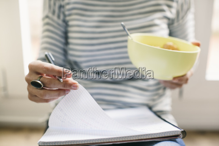 woman with muesli bowl and notepad