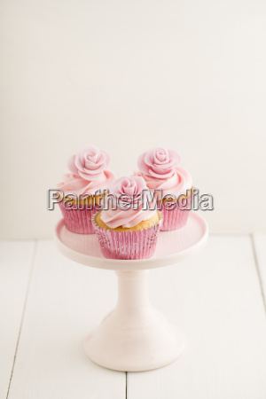 three pink cup cakes on a