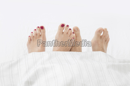 feet of couple in bed