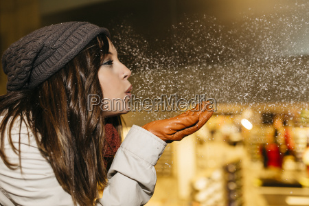 young woman blowing snow in the