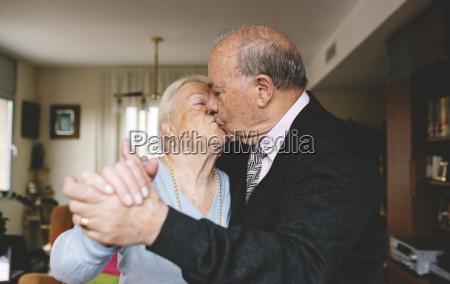 senior couple kissing and dancing at