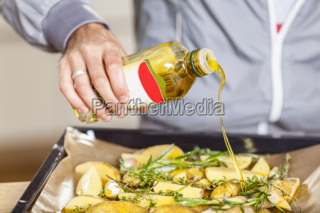 pouring oil over potato wedges on