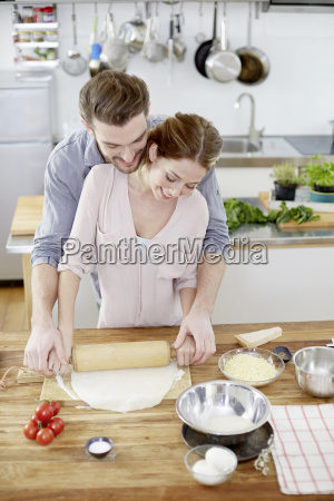 affectionate couple preparing pizza dough in
