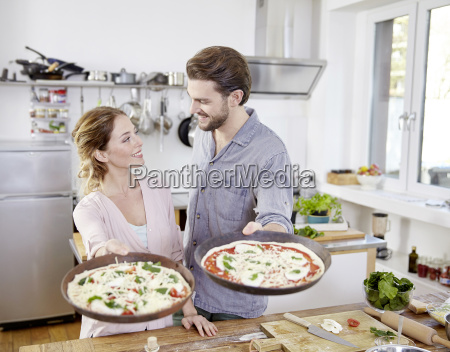 couple holding baking pans with raw