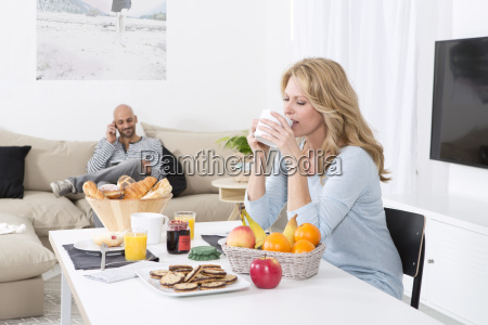 mature woman having breakfast while man