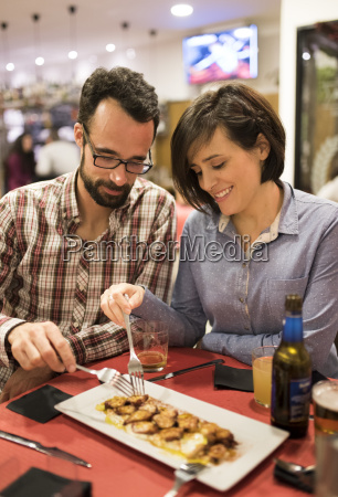couple eating cooked octopus in a