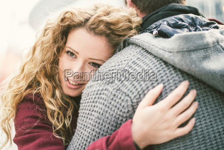 portrait of smiling young woman hugging