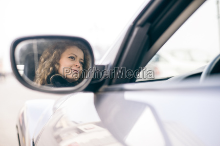 woman driving car mirrored in wing