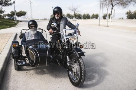 zwei biker stehen mit ihrem beiwagen