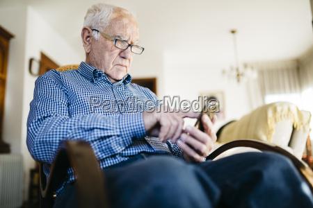 seniorenmensch mit smartphone zu hause