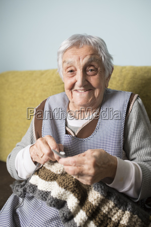 portrait of smiling senior woman knitting