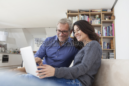 smiling couple at home on couch