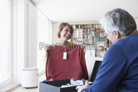 smiling woman showing husband her new