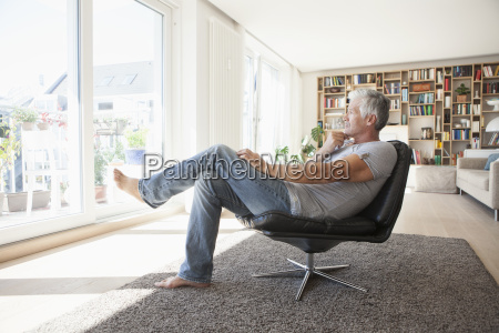 pensive man relaxing on leather chair