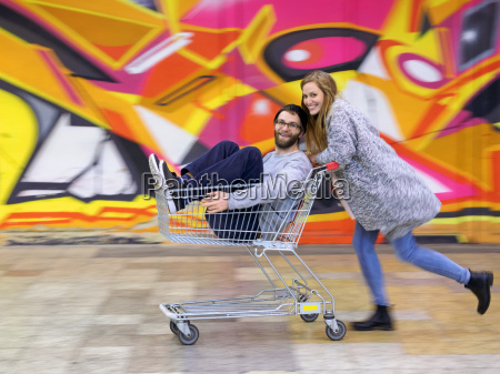 young woman pushing man in shopping